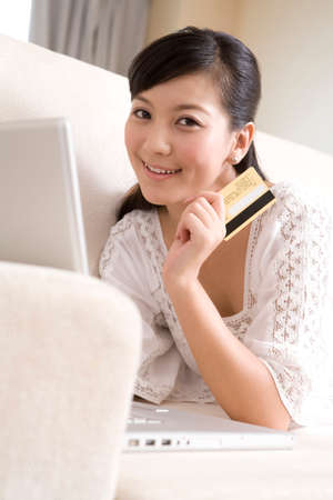 Asian woman with credit card and laptop LANG_EVOIMAGES