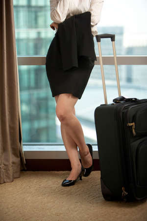 View of a woman in heels with her suitcase LANG_EVOIMAGES