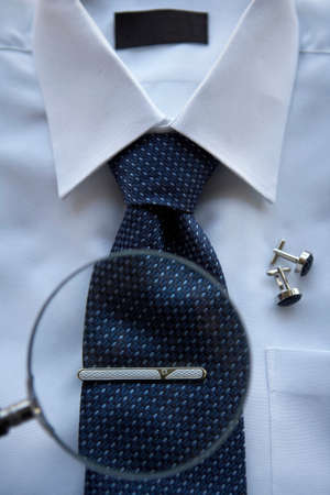 A Magnifying glass focused on a tie clip on a neck tie