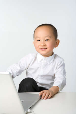 only boys: Young boy sitting with a laptop