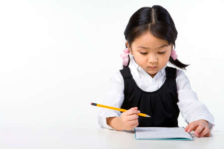 Little girl writes on a notebook LANG_EVOIMAGES