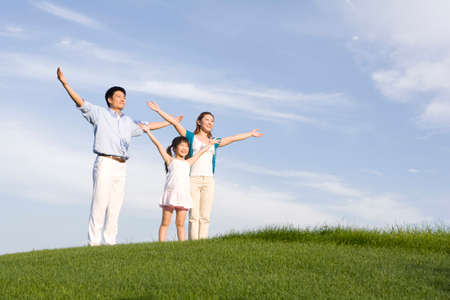 mujer mirando el horizonte: Family of three standing on the grass, arms out-stretched