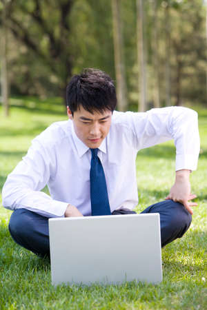 Businessman in the park with laptop