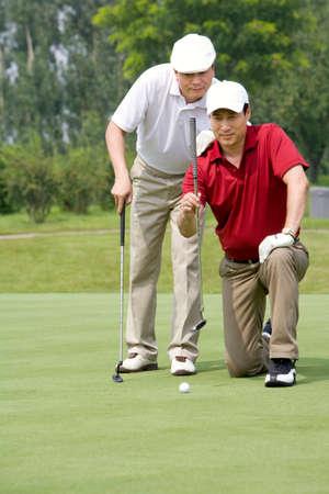 arrodillarse: Dos jugadores de golf masculinos en verde LANG_EVOIMAGES