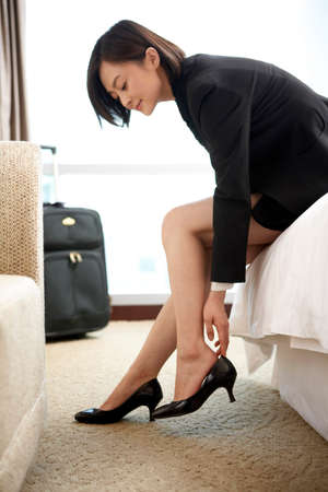 Woman in business attire putting on her shoes LANG_EVOIMAGES