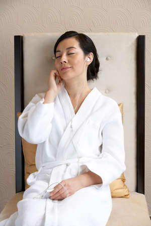 oriental bathrobe: Woman listening to music at a spa LANG_EVOIMAGES