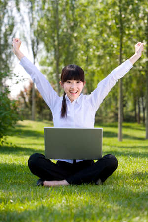 Woman in park with laptop LANG_EVOIMAGES
