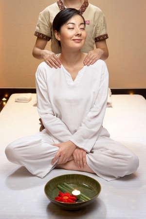 oriental bathrobe: Spa attendant giving a shoulder massage to woman