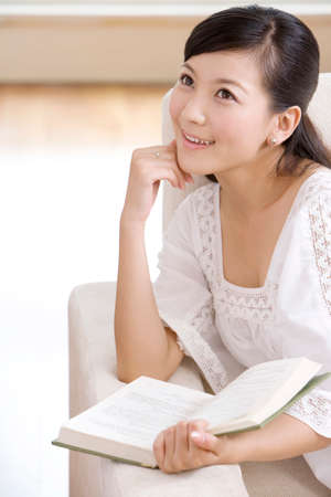 Asian woman reading on a sofa LANG_EVOIMAGES