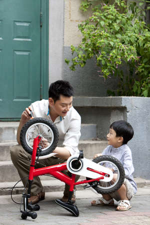 Young Chinese father and son fixing bike LANG_EVOIMAGES