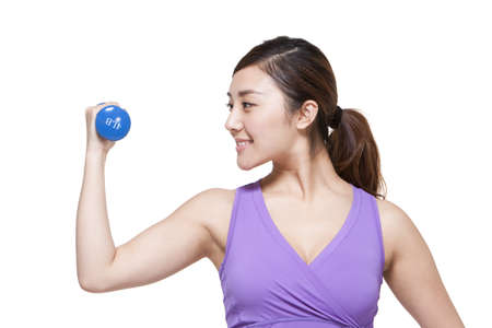 flexing: Young woman lifting weights
