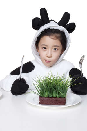 things that go together: Girl in a cow costume with a serving of grass on her plate