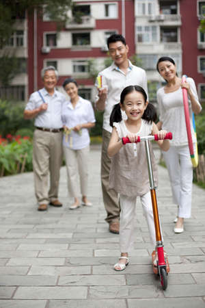 Chinese girl with scooter and family looking on