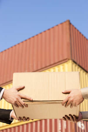 Businessman and shipping industry worker giving and receiving a cardboard box LANG_EVOIMAGES