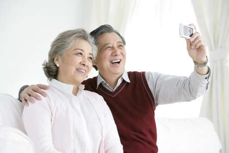 Senior Chinese couple taking self-portrait in living room LANG_EVOIMAGES