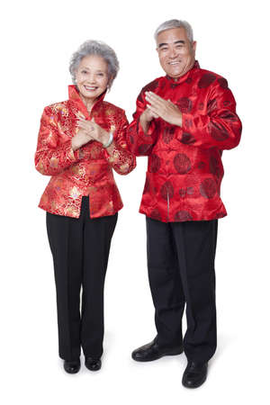 tang: Senior Couple Dressed in Traditional Clothing Celebrating Chinese New Year LANG_EVOIMAGES