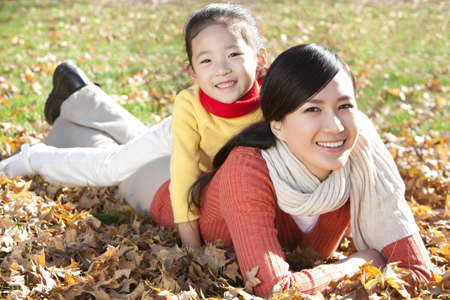 Mother and daughter lying on the grass in a park in Autumn