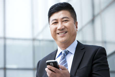 business: Happy businessman with mobile phone LANG_EVOIMAGES