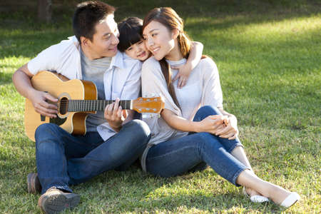 Young family in a park with a guitar LANG_EVOIMAGES