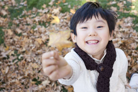Boy holding up a leaf in Autumn