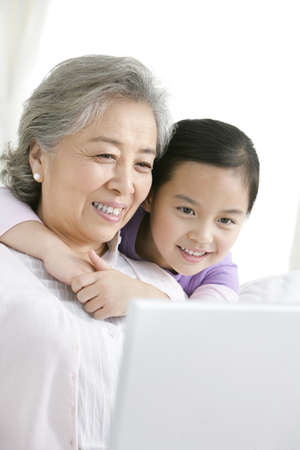 grandaughter: Chinese grandmother with grandaughter using a laptop