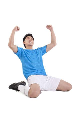puños cerrados: Jugador de fútbol arrodillado en el suelo en la celebración LANG_EVOIMAGES