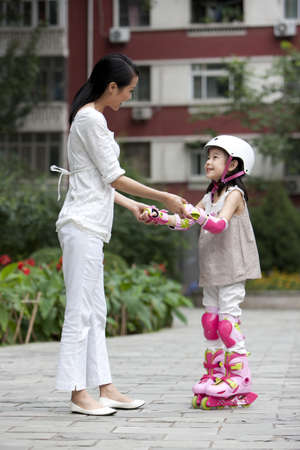 Chinese mother and daughter in rollerblades