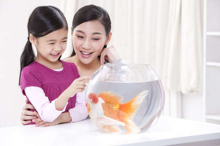 Mother and daughter having fun with goldfishes
