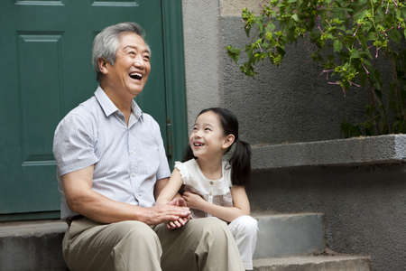 grandaughter: Chinese Grandfather and Grandaughter on front stoop LANG_EVOIMAGES