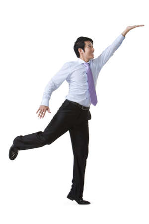 Businessman Reaching Up and Holding an Object