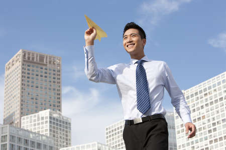 Businessman Throwing a Paper Airplane LANG_EVOIMAGES