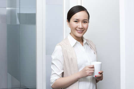coffeebreak: Smiling businesswoman during a coffeebreak LANG_EVOIMAGES