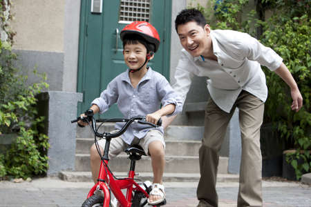 Young Chinese father training son to ride a bike LANG_EVOIMAGES