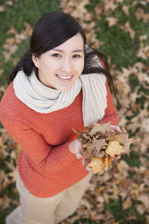 Young woman holding up Autumn leaves