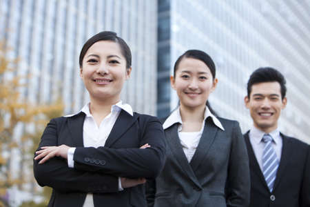three persons only: A team of businesspeople outside office buildings