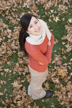 Young woman standing surrounded by Autumn leaves on the grass