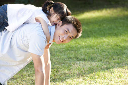 arrodillarse: Young Chinese father with daughter on piggyback outdoors
