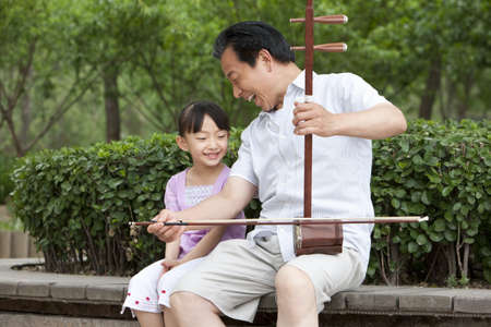 Grandfather playing Chinese traditional musical instrument Erhu