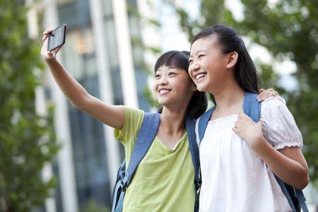 Cheerful schoolgirls taking self-portraits shots