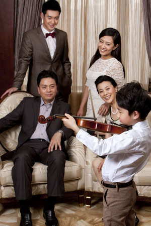 three generations of women: Little boy playing violin in front of family members
