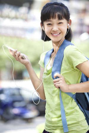 Portrait of cute schoolgirl holding smart phone