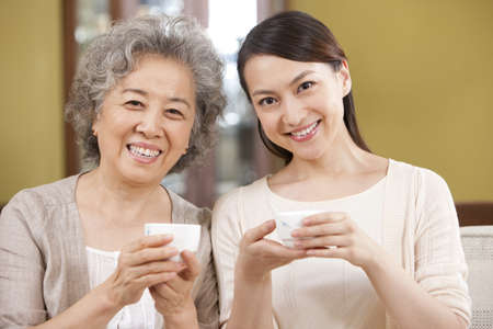 Portrait of young woman having tea with mother