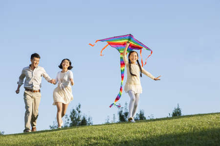 level playing field: Cheerful young family flying a kite in a park