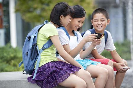 Schoolchildren playing smart phones together