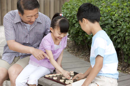 Grandfather playing Chinese chess with grandson and granddaughter
