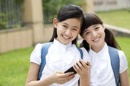 Excited schoolgirls in uniform with smart phone in school yard