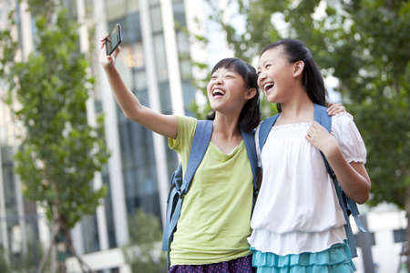 Cheerful schoolgirls taking self-portraits shots
