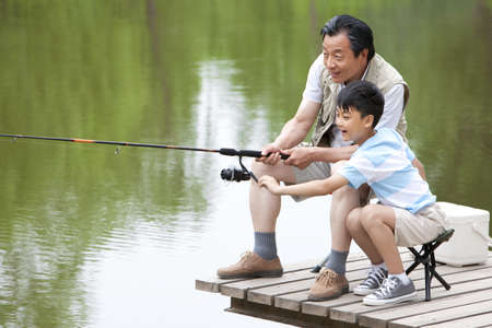 Grandfather teaching grandson fishing LANG_EVOIMAGES