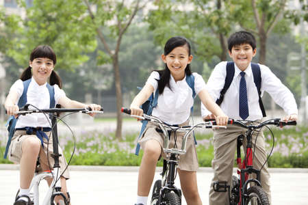 Happy schoolchildren in uniform with bicycles outdoors