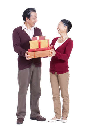 one mature woman only: Cheerful senior couple holding gift boxes